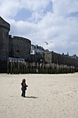 Child on the beach watching seagulls, St. Malo, Brittany, France, Europe
