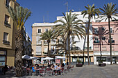 Palm trees and people at outdoor cafe seating at a square, Cadiz, Andalucia, Spain, Europe