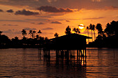 Sunset and fishermen hut at the westcoast of Koh Chang Island, Trat Province, Thailand, Asia