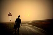 Abend, Altmodisch, Aussen, digital zusammengesetzt, ein, eine Person, Einsam, Ende, Erwachsene, Farbe, Flucht, Fortzüge, Geheimnis, geheimnisvoll, Going away, Horizont, Horizontal, Isolation, Landstraße, Leere Strasse, Mensch, menschlich, Monochrom, Schil
