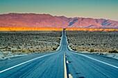 Sunrise on mountains over long straight two lane desert road, Anza Borrego Desert State Park, San Diego County, California