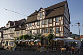 People enjoying an ice cream whilst seated outside a timberframe house in the old town, Rotenburg an der Fulda, Hesse, Germany, Europe
