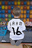 Young boy wearing a Phillip Lahm German National soccer team jersey at a dart booth at a funfair, Rotenburg an der Fulda, Hesse, Germany, Europe