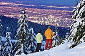 Skiers looking over Vancouver in the evening, British Columbia, Canada