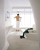 Man getting dressed, Hotel room on the 1st Floor, Designed by Zaha Hadid, Hotel Silken Puerta America, Madrid, Spain