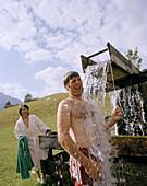 Man having a refreshing, cold shower, Outdoor shower, organic Hotel Chesa Valisa, Hirschegg, Kleinwalsertal, Austria