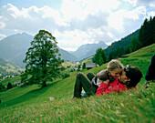 Mother and daughter lying on the grass having fun, Mountain meadows, Hirschegg, Kleinwalsertal, Austria