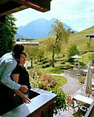 Couple on the balcony of an organic Hotel, Hirschegg, Kleinwalsertal, Styria, Austria