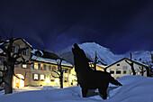 Dog figure in front of illuminated Hotel Meisser, Guarda, Engadin, Grisons, Switzerland, Europe