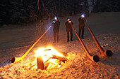 Alphorn players at a bonfire in the snow, Hemmersuppenalm, Reit im Winkl, Chiemgau, Upper Bavaria, Bavaria, Germany, Europe