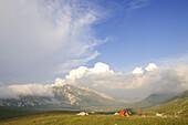 Hiker with tent at Campo Imperatore, Monte Prena, Monte Camicia, Gran Sasso National Park, Abruzzi, Italy, Europe