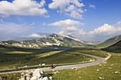 Cyclist on country road at Campo Imperatore, Monte Prena, Monte Camicia, Gran Sasso National Park, Abruzzi, Italy, Europe