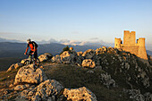 Mountain biker in front of castle Rocca Calascio, Campo Imperatore, Gran Sasso National Park, Abruzzi, Italy, Europe