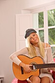 Adult, Adults, At home, Blonde, Blondes, Cap, Caps, Caucasian, Caucasians, Color, Color image, Colour, Contemporary, Daytime, Facing camera, Fair-haired, Female, grin, grinning, Guitar, Guitars, Hat, Hats, Headgear, Hobbies, Hobby, Home, human, indoor, in