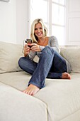 Adult, Adults, At home, Barefeet, Barefoot, Blonde, Blondes, Blue jean, Blue jeans, Caucasian, Caucasians, Color, Color image, Colour, Contemporary, Couch, Couches, Daytime, Denim, Earphone, Earphones, Facing camera, Fair-haired, Female, Full body, Full l