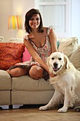 Adult, Adults, Animal, Animals, At home, Brunette, Brunettes, Caucasian, Caucasians, Color, Color image, Colour, Companion, Companions, Contemporary, Couch, Couches, Dark-haired, Dog, Dogs, Domestic animal, Domestic animals, Facing camera, Female, Full bo