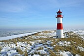 Lighthouse List East on snow covered dunes with a bright blue sky at a sunny day with icy sea in the background, Sylt, Northfrisian Islands, Schleswig-Holstein, Northern Germany, Europe