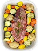 An uncooked lamb roast with vegetables in a baking tray