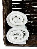 A stack of bath towels isolated in a wicker basket