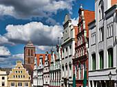 Houses along Kramerstrasse, St. Nikolai Church in background, Hanseatic city of Wismar, Mecklenburg-Vorpommern, Germany