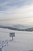 Sign in snow- covered landscape at Wasserkuppe, near Gersfeld, low mountain range, Rhoen, Hesse, Germany