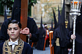 Child And Penitents In Black Cowl And Hood, Procession Of The Christ Of Faith And Pardon, Holy Week For The Easter Holidays, (The Passion Of Christ), Madrid, Spain