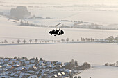 Aerial view of a two-seater autogyro, gyrocopter above a winter landscape, Lower Saxony, Germany
