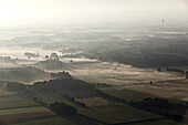 Aerial of flat, North German landscape in the morning mist, Lower Saxony, Germany
