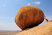Woman pushing red balancing granite rock from slab, Great Spitzkoppe, Namibia