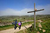 Pilgrims at a wayside cross in the sunlight, Province of Leon, Old Castile, Castile-Leon, Castilla y Leon, Northern Spain, Spain, Europe