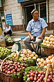 A fruit vendor selling his fruits in the vibrant markets in the old city of Kashgar, China.