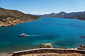 Excursion boat seen from the Venetian fortress, Island of Spinalonga, Lasithi prefecture, Gulf of Mirabella, Crete, Greece