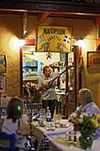 Man playing instrument, old venetian port, Rethymnon, Crete, Greece