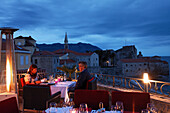Couple on the terrace of the Astoria restaurant in the evening, view of citadel, Budva, Montenegro, Europe