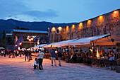 Restaurants along the city wall in the evening, Budva, Montenegro, Europe