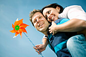 Mid adult man giving woman with pinwheel a piggyback ride, Styria, Austria