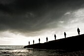 Silhouettes of 7 people standing on a sea wall