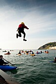 Members of Aberystwyth Kayak Club kayaking and jumping into the sea at Aberystwyth Wales UK