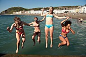 Four young women Aberystwyth university students jumping into the sea at the end of the academic year, June 2009, Wales UK