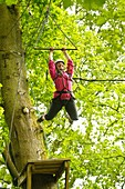 Teenagers on high ropes in the trees as part of a course organised by the Canolfan Yr Urdd outward bound adventure centre, Glanllyn, Bala, North Wales UK