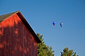 Battle Creek, Michigan - The National Hot Air Balloon Championships Two balloons float over a barn