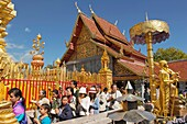 People walking around the main pagoda in ritual ceremony in Wat Phrathat Doi Suthep Chiang Mai, Thailand