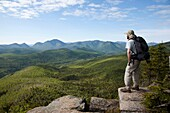 Zealand Notch - A hiker takes in the views from the summit of Zeacliff during the summer months Located along the Appalachian Trail in the White Mountains, New Hampshire USA