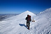 A winter hiker heading north on the Appalachian Trail in extreme weather conditions during the winter months in the White Mountains, New Hampshire USA Mount Madison is in the background