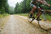 Man biking on Rob Brook Road in Albany, New Hampshire USA This dirt road follows parts of the old Bartlett and Albany Railroad which was a logging railroad in operation from 1887 - 1894