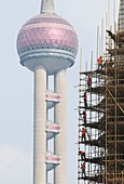 Construction workers on scaffolding near the Oriental Pearl Shanghai China