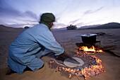 homme mettant de la pate a pain a cuire dans le sable chauffe par les braises, desert de l'Aïr, Niger, Afrique de l'Ouest//man cooking bread in sand for Taguela, Aïr, Niger, Western Africa