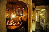 two young women tasting wine in the cellar of Gloria restaurant, Tallinn, estonia, northern europe