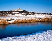 Glastonbury Tor viewed over the River Brue on South Moor in winter snow Glastonbury, Somerset, England, United Kingdom