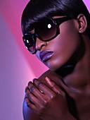 Beautiful young woman in black sunglasses on purple background Beauty headshot